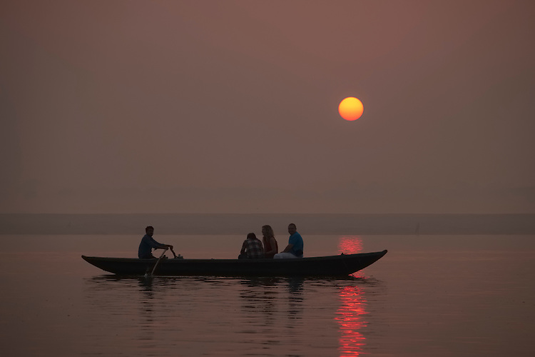 A misty sunrise silhouettes a small boat on the Ganges in front of the Ghats of Varanasi.