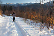 Man snowshoeing along the Forest Discovery Trail in Lincoln, New Hampshire during the winter months. This trail is a living classroom in ecological management in the White Mountain National Forest.