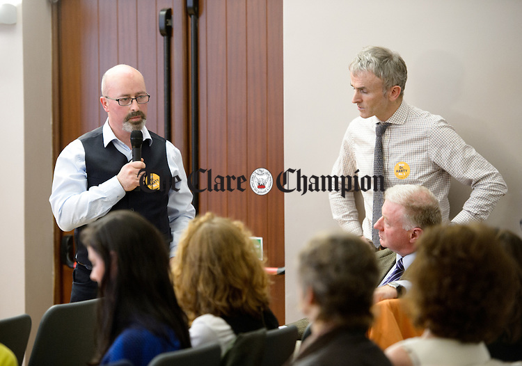 Dr Conor Magee of Scariff speaking watched by Dr. Fergus Glynn at a public meeting as part of the #nodoctornvillage campaign in Corofin Hall. The meeting ratified Dr. Michael Harty as the Clare GP candidate for the forthcoming General election. Photograph by John Kelly.