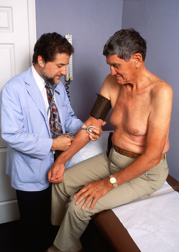 A male medical doctor checks the blood pressure of a senior patient.
