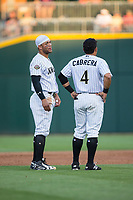 Yoan Moncada (10) and Everth Cabrera (4) of the Charlotte Knights wait for teammates to bring them their hats and gloves between innings of the game against the Durham Bulls at BB&T BallPark on May 15, 2017 in Charlotte, North Carolina. The Knights defeated the Bulls 6-4.  (Brian Westerholt/Four Seam Images)