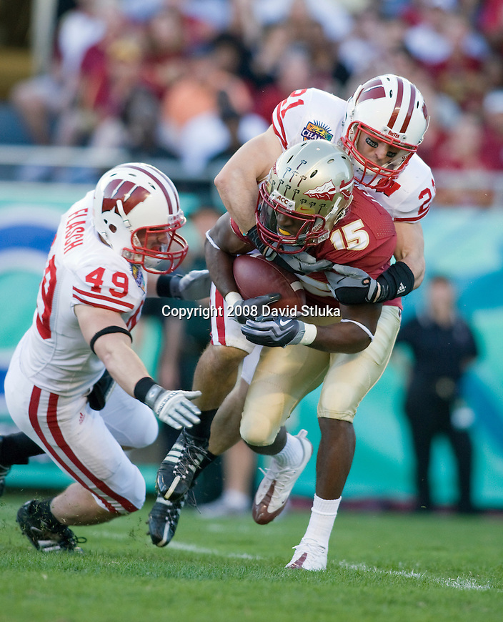 ORLANDO, FL - DECEMBER 27: Chris Maragos #21 and Ryan Flasch #49 of the Wisconsin Badgers tackle Louis Givens #15 of the Florida State Seminoles during the Champs Sports Bowl on December 27, 2008 at the Citrus Bowl in Orlando, Florida. Florido State beat Wisconsin 42-13. (Photo by David Stluka)
