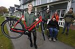 Foto: VidiPhoto<br /> <br /> TILBURG – Een onverwachte verrassing voor de 27-jarige fietsfanaat Lobke uit Tilburg vrijdag. Haar 17 jaar oude rode Batavus was na 62.000 kilometer (anderhalf keer de wereld rond) toe aan vervanging, maar haar favoriete retro rode kleur bleek niet meer verkrijgbaar. Dus schreef ze de fietsfabrikant uit Heerenveen een persoonlijke brief. Voor Batavus was dat reden de productielijn even te onderbreken en speciaal voor Lobke een in retro rood gespoten fiets te fabriceren. Precies op haar verjaardag vrijdag, kreeg Lobke de fiets officieel overhandigd.