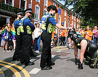 A man dressed in a leather outfit approaches police officers in this year's Pride Parade in the centre of Cardiff, Wales, UK. Sayurday 26 August 2017
