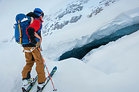 A skier stands looking into a crevasse during the Öztal ski tour, Austria