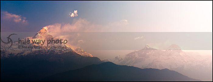 Machapuchare, aka Fishtail, is basking in early morning sunlight. Annapurna mountains on the right in fog.