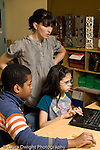 Public Middle School Grade 6 boy and girl working together at laptop computer female science teacher lookig at their work vertical
