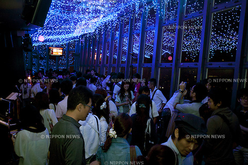 July 7, 2012, Tokyo, Japan - Visitors to the main observatory of Tokyo Tower contemplates the LED lights that illuminate the place, lighting represent Orihime (the female figure), white lights represent Hikoboshi  (the male figure) and blue light the Milky Way in commemoration of the festival of Tanabata. The annual celebration of Tanabata in Japan and has been held since the Edo era. It celebrates the meeting of two lovers Orihime and Hikoboshi, according to legend the Milky Way separates these lovers, and may only meet once a year on the seventh day of the seventh month of calendar. (Photo by Rodrigo Reyes Marin/AFLO)....