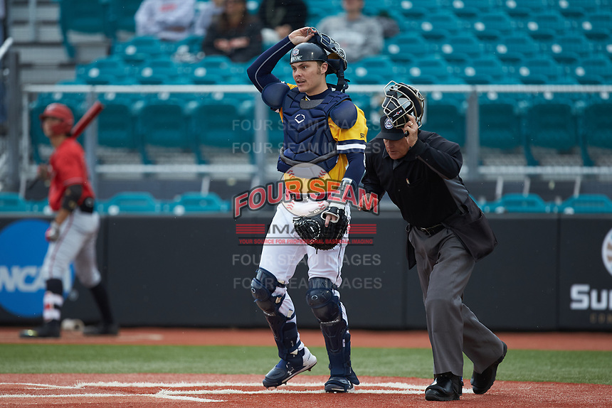 UNCG Spartans catcher Ryan Caveness (10) and home plate umpire Mac Smith track the ball during the game against the San Diego State Aztecs at Springs Brooks Stadium on February 16, 2020 in Conway, South Carolina. The Spartans defeated the Aztecs 11-4.  (Brian Westerholt/Four Seam Images)