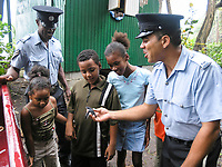 local police show leatherback sea turtle hatchlings, Dermochelys coriacea, to local children before release, Dominica, Caribbean, Atlantic