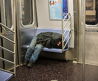 Homeless man takes up several seats as he sleeps in a subway car in New York on Monday, January 6, 2014. (© Richard B. Levine)