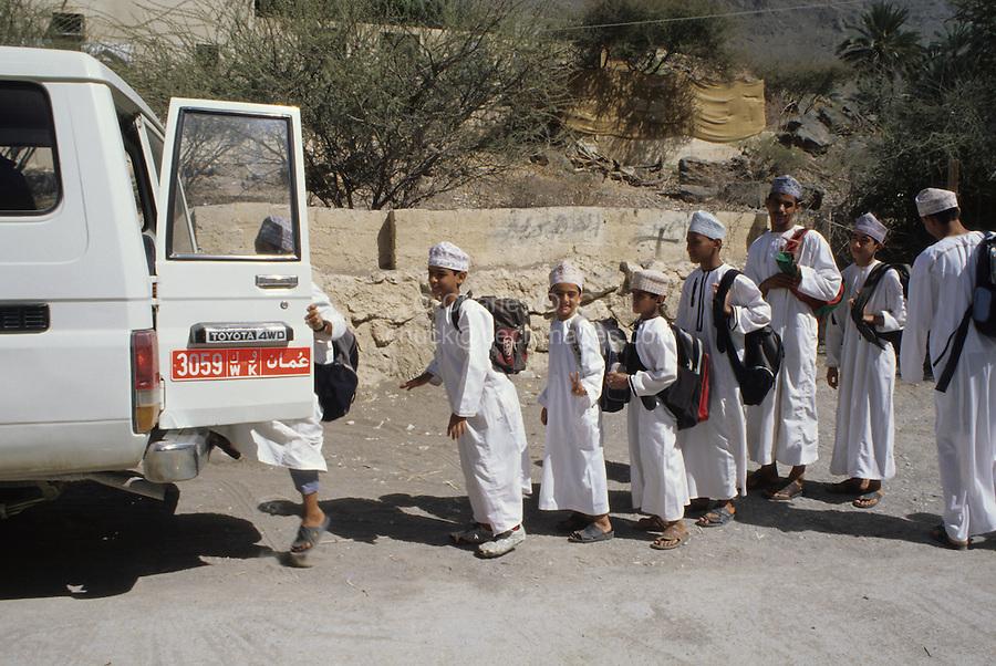 Wadi Bani Kharus, Oman, Arabian Peninsula, Middle East - Omani Schoolboys Getting into School Bus.