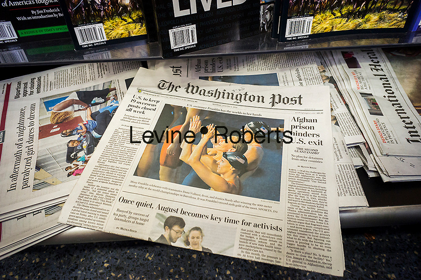 The Monday, August 5, 2013 edition of the Washington Post is seen on a newsstand in New York.  Jeff Bezos, the billionaire founder of Amazon, is purchasing the Washington Post Company, including the flaship paper, for a reported $250 million. The purchase is through Bezos and is not affiliated with Amazon. (© Richard B. Levine)