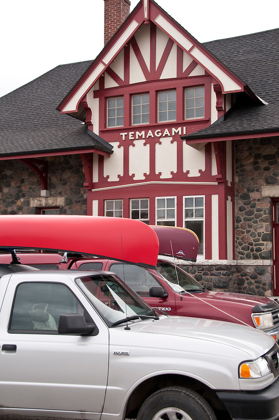 Trucks with canoes on top parked at the Temagami train station in Temagami Ontario Canada.
