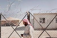 40 year old Khaled Saeed waits outside a fenced-off area where all newly arrived people must wait during initial processing. Khaled is waiting to greet a former neighbour. If they are accepted they will be given one tent per family, a food ration and basic necessities like mattresses and a small cooking set. Khaled decided to flee his home when his 11 year old son, who was guarding cows in a field, was killed by a bomb on 3 March 2013. Approximately two million people have fled the conflict in Syria. At least 130,000 of them live in Zaatari Refugee Camp, although it was designed to house 60,000, and a further 2,000 people arrive each day.