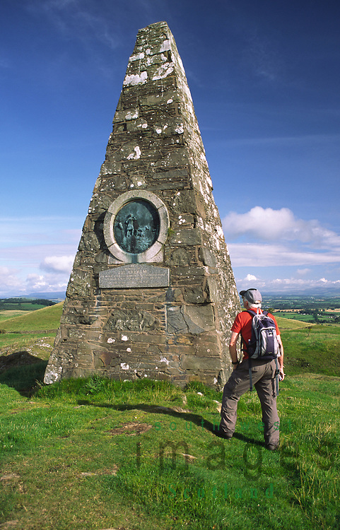 Joe Grahams Monument on Almagill Hill near Dalton on Annandale Way with walker Dumfriesshire Scotland UK