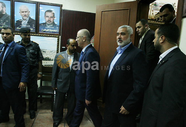 Palestinian Prime Minister Rami Hamdallah walks with senior Hamas leader Ismail Haniyeh as he during his visit to the Gaza Strip, at Haniyeh's house in Gaza city on October 9, 2014. The Palestinian unity government which took the oath of office in June under technocrat prime minister Rami Hamdallah arrived to Gaza Strip on Thursday to convene the first fully meeting. Hamdallah said that the unity government will rebuild the bombed-out Gaza Strip following a seven-week Israeli offensive. Photo by Abed Rahim Khatib