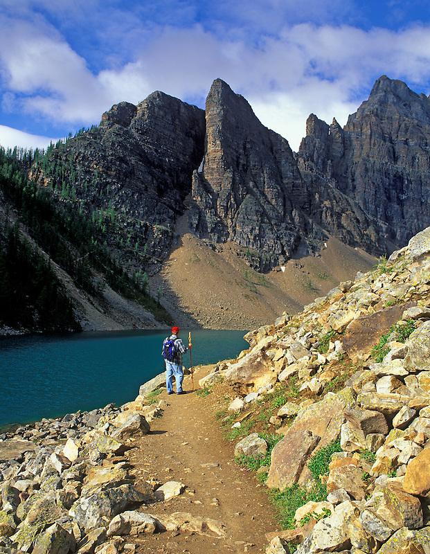Hiker on path around Agnes Lake. Banff National Park, Canada