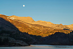 Full moon setting over mountains at sunrise over Ellery Lake, near Tioga Pass, Eastern Sierra, California
