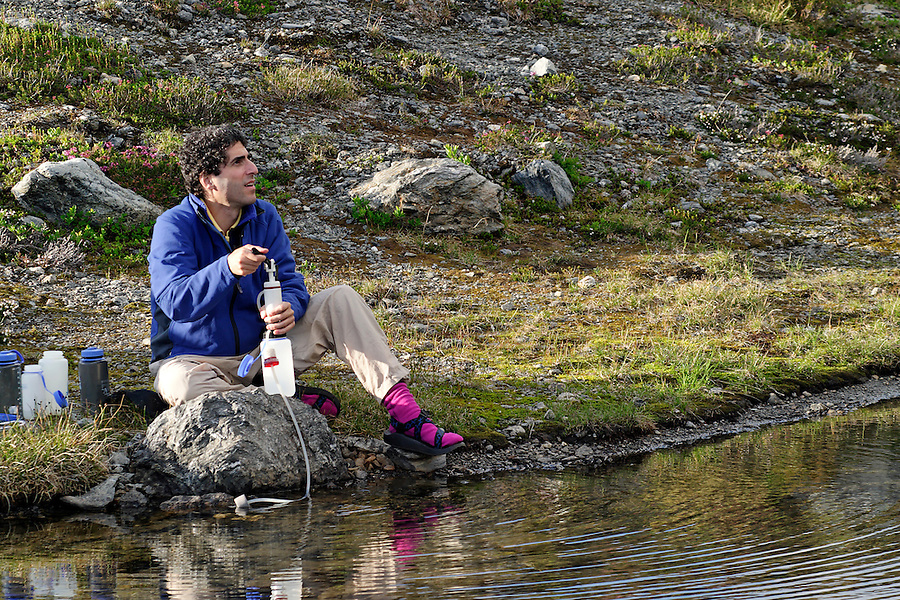 Man sitting on lake shore pumping water, near Yellow Aster Butte, North Cascades, Whatcom County, Washington, USA