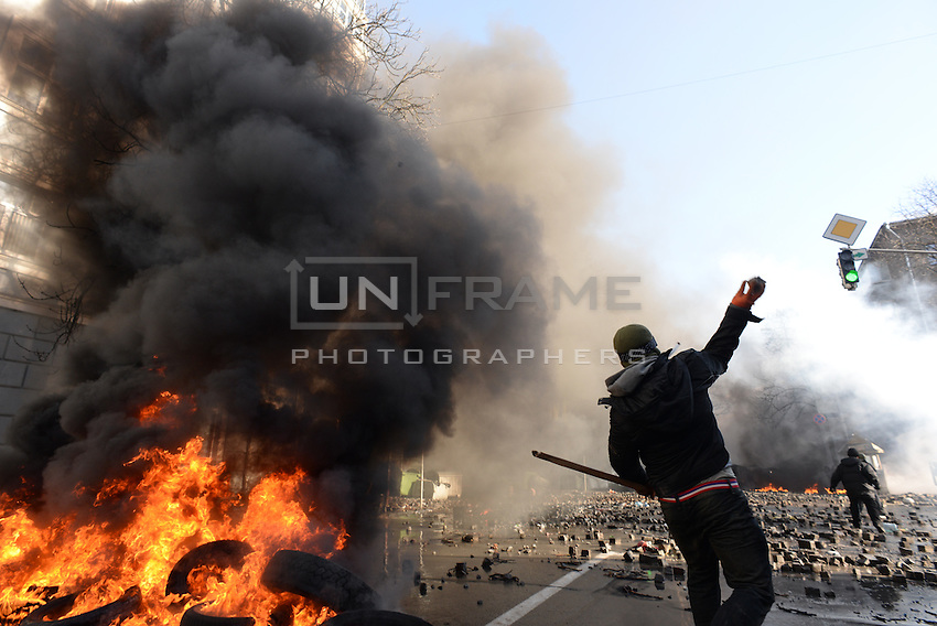 Rioters hurls paving stones beyond the barricades. Kiev, Ukraine