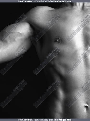 Artistic photo of a young man with lean muscular body, closeup of torso in biceps isolated on black background Black and white