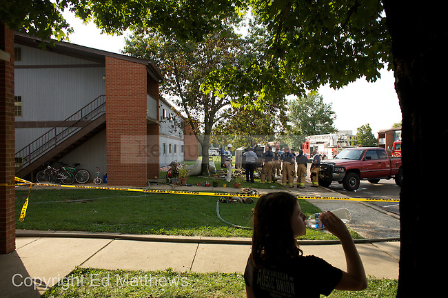 Nine-year-old Kayla Adkins stands under the shade of a tree while firefighters continued to search a Greg Page apartment building that was damaged by fire on Monday, Aug. 26, 2009. The fire started in one apartment, but spread to two others before it was extinguished said Ben Crutcher, UK's Associate Vice President of Auxiliary Services. All eight units in the building will be vacated, he said...Photo by Ed Matthews