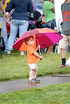 A boy watching a parade from under an umbrella.
