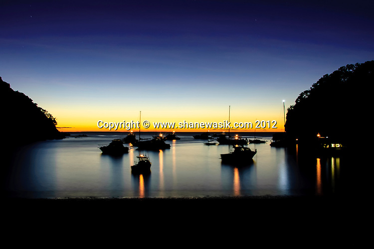 Sunrise at south east bay, Mayor Island / Tuhua. The lights of the boats at anchor illuminating the bay.