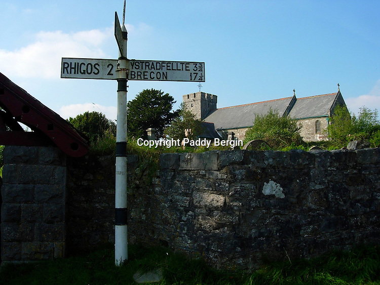 Signpost in Mid-Wales, Brecon being the nearest town. Notice the old stone wall and the stone church in the background.<br />