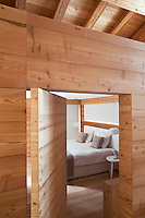 A thick wooden door which pivots both ways opens into the simply furnished bedroom