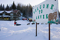 Ray Redington Jr. runs up bank of the Yukon River as he passes the *Welcome to Anvik* sign