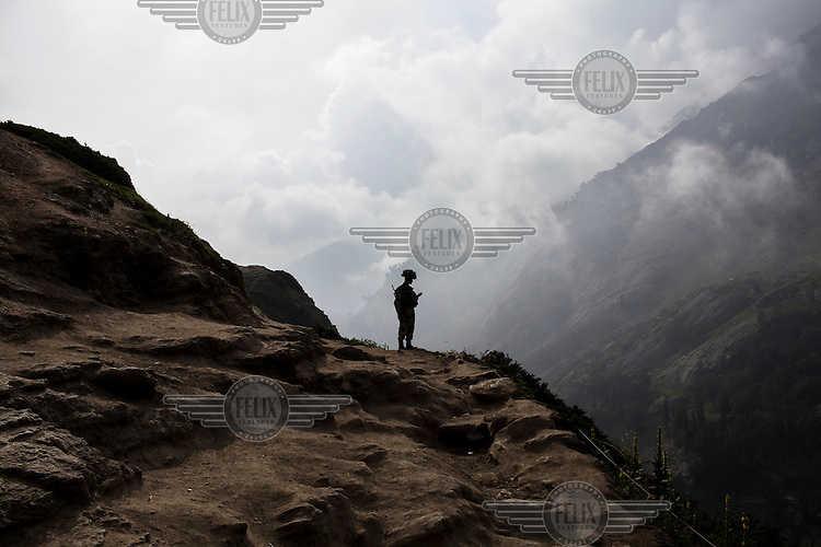 A soldier patrols and provides security along the Amarnath trekking route in Kashmir. Hindu pilgrims brave sub zero temperatures and high altitude passes and make their pilgrimage to reach the sacred Amarnath cave, which houses a lingam - a stylized phallus, worshipped by Hindus as a symbol of God Shiva.