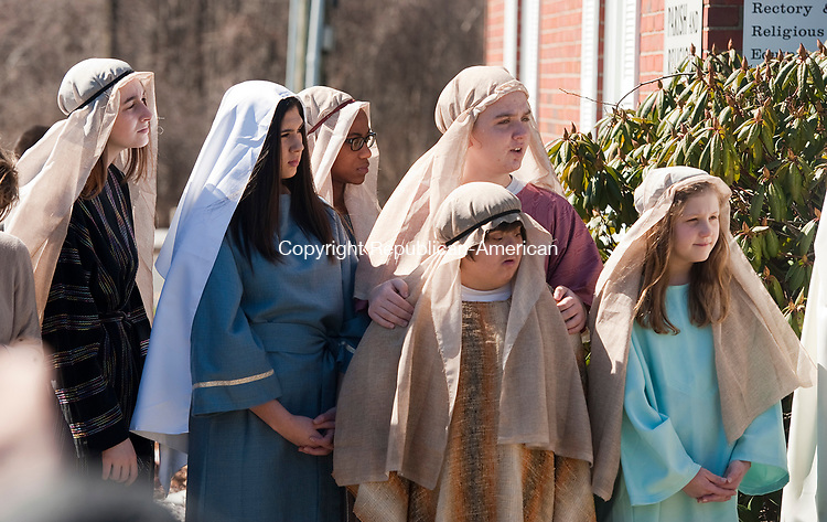 PROSPECT, CT-040917JS01-Students portraying apostles, looks on as Rev. Grzegorz Jaworowski blesses the palms that would be handed out to parishioners during Palm Sunday at St. Anthony's Church in Prospect. The procession of a student portraying Jesus, walking with a donkey, was followed by a Mass. <br />  Jim Shannon Republican-American