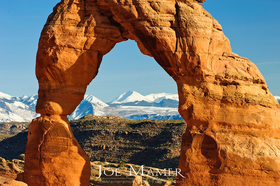 Snow covered La Sal Mountains seen through Delicate Arch in Arches national Park, Moab, Utah.