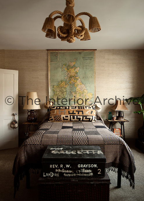 A guest bedroom features a conglomerate of exotic furniture pieces and collectables giving the room an other-worldly, exotic feel, such as the bedside lamps, which are West German ceramics from the 70s.  This theme is beautifully accentuated by a textured Philip Jeffries wallpaper made of split bamboo on grass cloth.