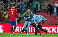 a pitch invader is tackled by stewards as he looks for a photo with Alvaro Morata of Spain during the International Friendly match between England and Spain at Wembley Stadium, London, England on 15 November 2016. Photo by Andy Rowland.