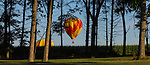 Balloons drift softly past a grove of trees north and east of Indianola.