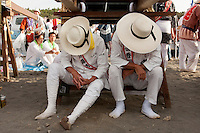 Mikoshi supporters wearing large brimmed hats rest under a mikoshi during the Hamaorisai Matsuri that takes place on Southern Beach in Chigasaki, near Tokyo, Kanagawa, Japan Monday July 20th 2009. The festivals marks the celebration of Marine Day and the rescuing of a divine image that was washed ashore in the area. Over thirty Mikoshi or portable shrines are carried through the night from surrounding shrines to arrive on the beach for sunrise. There they are blessed and then carried into the surf to purify them.