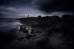 A dark, stormy scene at Newport beach at sunset, creating dark blue clouds and shadows, silhouette of a man at the end of the rocks