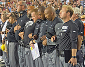 "Oakland Raiders coaches stand with locked arms in solidarity as the National Anthem is sung prior to the game against the Washington Redskins at FedEx Field in Landover, Maryland on Sunday, September 24, 2017.  The Raiders chose to demonstrate prior to their nationally televised contest following tweets earlier in the day from United States President Donald J. Trump urging owners to ""fire or suspend"" players who participated in the protests by not standing for the anthem.<br /> Credit: Ron Sachs / CNP"