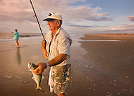 An elderly man is up bright and early, surf fishing at the South Core Banks, North Carolina