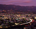 Santa Barbara at sunset with city lights and car traffic with light car streaks on highway 101 with Santa Ynez Mountain Range in background, Santa Barbara, California USA