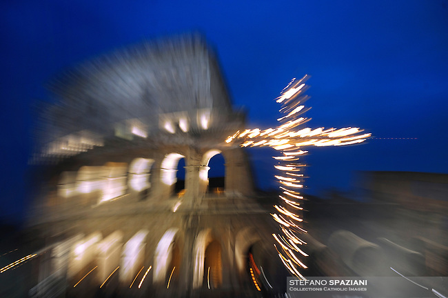Pope Benedict XVI holds the wooden cross during the Via Crucis (Way of the Cross) torchlight procession on Good Friday in front of the Colosseum in Rome, Friday, April 10, 2009.