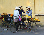 "Three Vietnamese female ""bike-vendors"" take a moment to visit, as they stand by their parked bicycles laiden with baskets of fruit, and sampe their wares and chat. The women are wearing clothes typical of vendors: long, dark pants, long-sleeved shirts untucked, coolie hats and scarves used to cover their mouths as protection from polution."