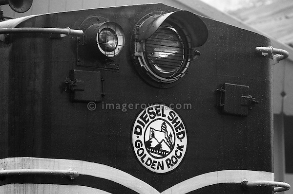 Diesel locomotive of the Nilgiri Mountain Railway on a foggy day at Ooty railway station. India, Tamil Nadu, Ooty 2005. --- Info: The Nilgiri Mountain Railway (NMR) is the only rack railway in India and connects the town of Mettupalayam with the hill station of Udagamandalam (Ooty), in the Nilgiri Hills of southern India. The construction of the 46km long meter-gauge singletrack railway in Tamil Nadu State was first proposed in 1854, but due to the difficulty of the mountainous location, the work only started in 1891 and was completed in 1908. This railway, scaling an elevation of 326m to 2,203m and still in use today, represented the latest technology of the time. In July 2005, UNESCO added the NMR as an extension to the World Heritage Site of the Darjeeling Himalayan Railway.