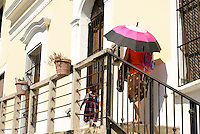 Woman carrying a parasol and a young girl  in Old Mazatlan, Sinaloa, Mexicoin old Mazatlan, Sinaloa, Mexico