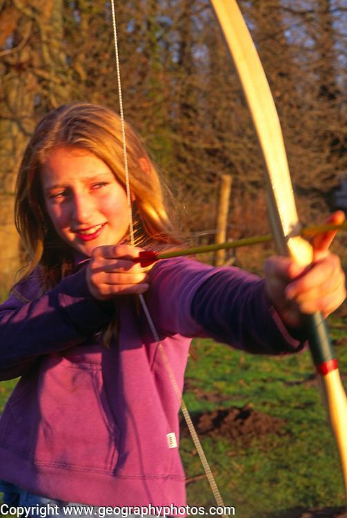 A293J7 Girl firing toy bow and arrow