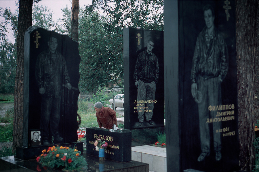 Ekaterinburg, Russia, 24/08/2000..The graves of murdered members of the Uralmash Gang, one of the cty's most notorious mafia groups, in their private plot at the Northern Cemetery..A woman looking at the recent grave of gang member Alexander Kruk, surrounded by tombs of his slain comrades.