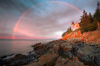 A double rainbow appears briefly at sunrise over Bass Harbor Head Lighthouse, which is reflected in a tidal pool as it overlooks the entrance to Bass Harbor and Blue Hill Bay in Tremont, Maine, located within Acadia National Park in the southwest portion of Mount Desert Island.